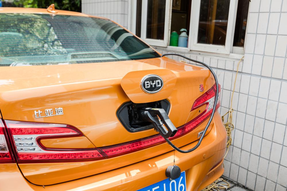 חלק אחורי של רכב חשמלי כתום של חברת BYD מחובר לעמדת טעינה