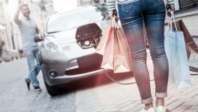 אישה וגבר עומדים ליד מכונית חשמלית מחוברת לעמדת טעינה