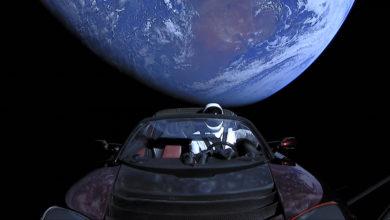 רכב טסלה רודסטר עם בובה בתוכו בחלל עם רקע של כדור הארץ
