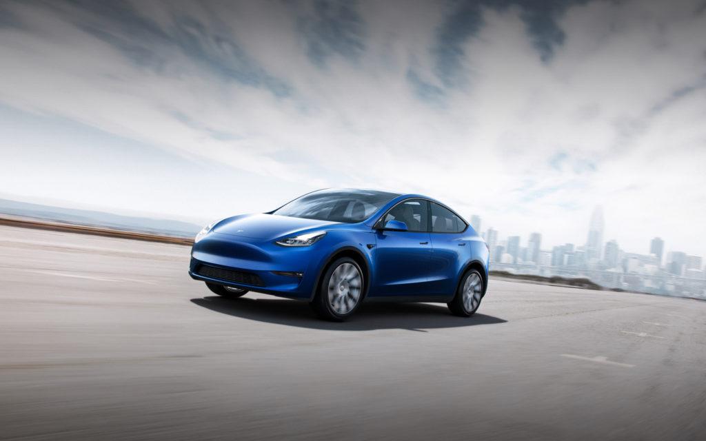 רכב מסוג טסלה מודל Y כחול נוסע על כביש