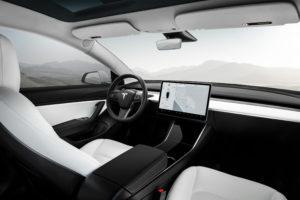 פנים הרכב של טסלה מודל 3 עם מושבים לבנים ומסך 15 אינטש