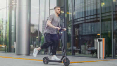 גבר רוכב על קורקינט חשמלי בעיר