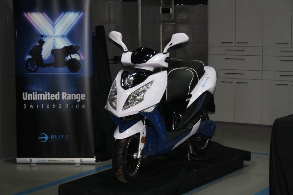 הקטנוע החדש באירוע ההשקה, קטנוע חשמלי בצבע לבן עם באנר של החברה מאחור
