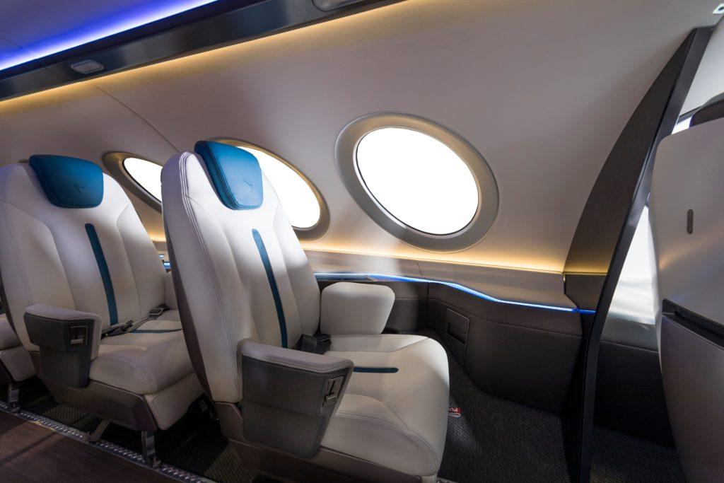 כסאות הנוסעים בפנים המטוס בצבעים לבן וכחול עם חלונות עגולים ליד כל מושב