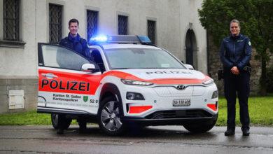 רכב משטרתי שוויצרי חשמלי מסוג יונדאי קונה עם שוטרת ושוטר עומדים לידו