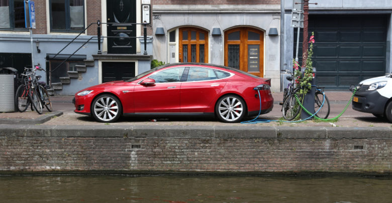 רכבים חשמליים בינהם טסלה מודל S אדומה מחוברים לעמדת טעינה ליד תעלה באמסטרדם