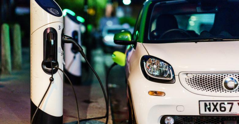 רכב חשמלי קטן ולבן מחובר לעמדת טעינה ברחובות לונדון