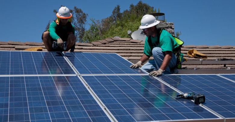 שני עובדים מתקינים פאנלים סולאריים על גג בקליפורניה ארצות הברית