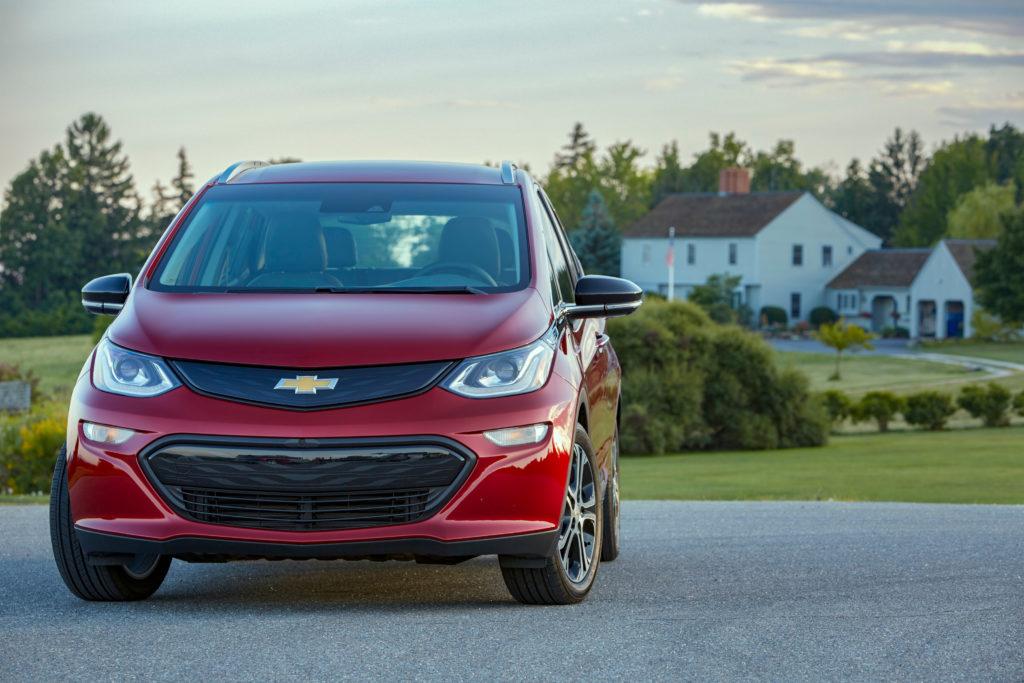 שברולט בולט EV בצבע אדום מבט מקדמת הרכב כשמאחור בית ונוף ירוק