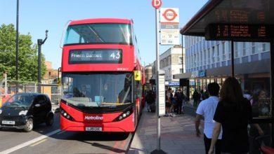 אוטובוס חשמלי דו-קומתי אדום עוצר בתחנה בלונדון