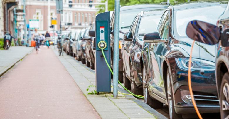 רכבים חשמליים מחוברים לעמדות טעינה בסמוך לשביל אופניים באמסטרדם.