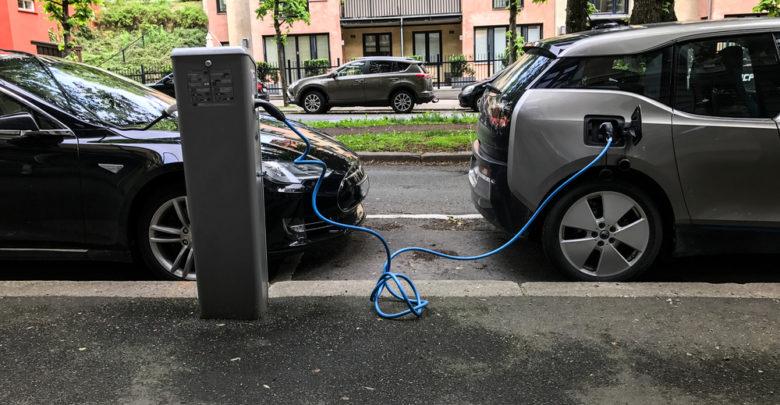 שני רכבים חשמליים מחוברים לעמדת טעינה ביום בהיר בנורווגיה