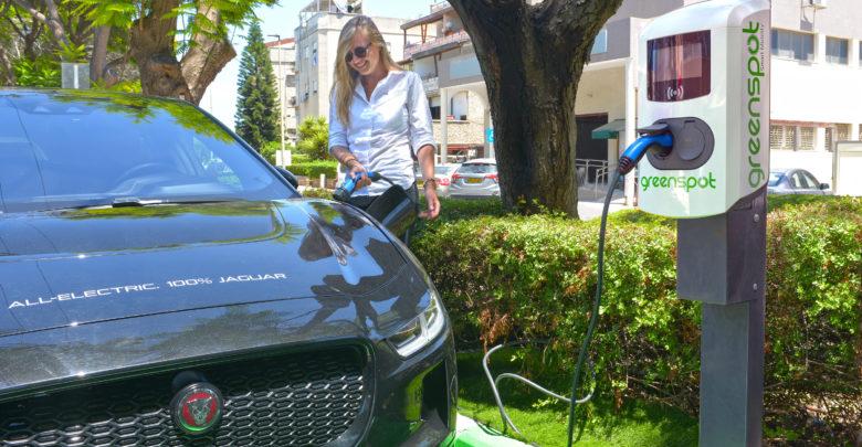 אישה מחברת יגואר חשמלית לעמדת טעינה של חברת גרינספוט