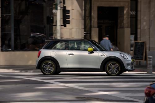 מיני קופר חשמלית לבנה בכביש בעיר