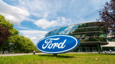 שלט עם הלוגו של פורד בכחול כשמאחוריו מבנה של החברה