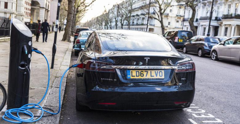 טסלה מודל S שחורה ברחובות לונדות מחוברת לעמד טעינה
