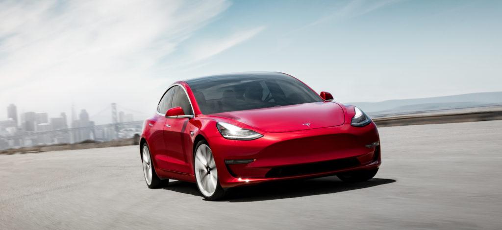 טסלה מודל 3 בצבע אדום על הכביש, מבט מקדמת הרכב כשמאחור עיר ובניינים רחוקים