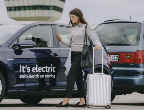 אישה עם טרולי עומדת לידר רכב חשמלי של פולקסווגן עם הכיתוב It's electric על הרכב