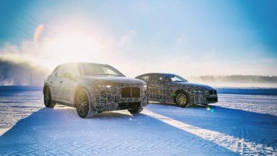 שני דגמים חשמליים של חברת BMW בסדרת בדיקות בחורף על משטח שלג, מכוסים במדבקות שחורות לבנות