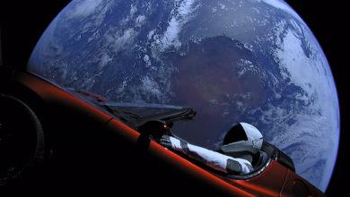טסלה רודסטר עם בובה בתוכה בחלל כשברקע כדור הארץ