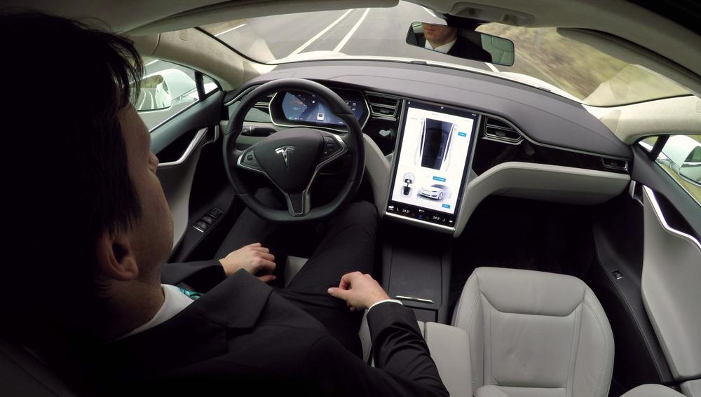 איש עסקים בתוך טסלה מודל S כשהנהיגה האוטונומית מופעלת