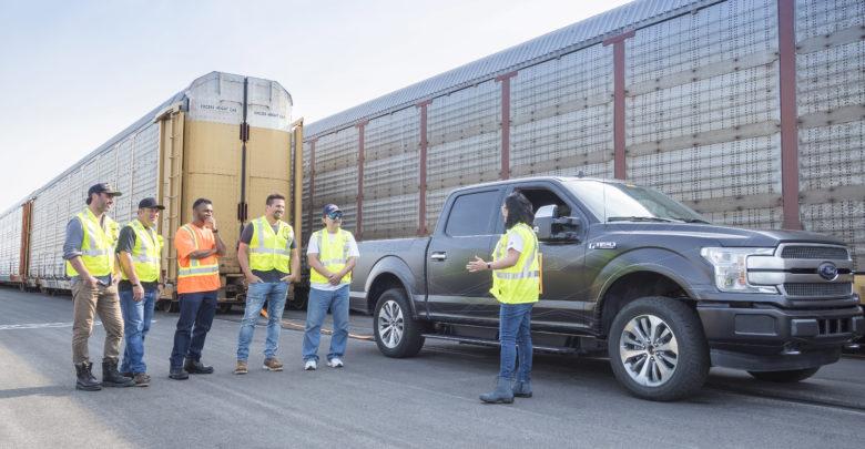 פורד FF-150 חשמלית עומדת בכביש כשמאחוריה קרונות רכב ומלפנים נהגים לבושים באפודים זוהרים