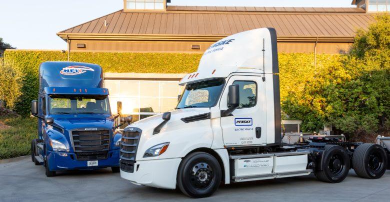 שתי משאיות סמי טריילר חשמליות ללא מטען של חברת דיימלר, אחת בצבע לבן ואחת בצבע כחול