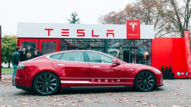 טסלה מודל S אדומה חונה ממול לאולם תצוגה של החברה