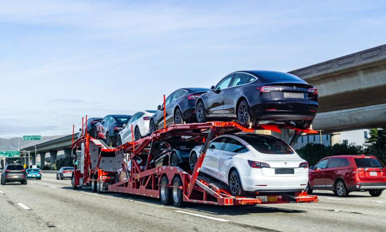 מובילית רכב אדומה עם רכבי טסלה מודל 3 חדשים על כביש מהיר בסן פרנסיסקו
