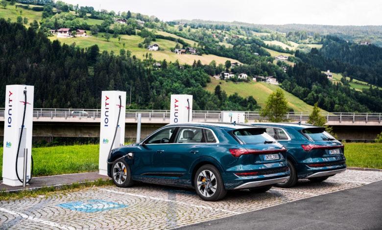 רכבי אאודי אי-טרון חשמליים מחוברים לעמדת טעינה של IONITY כשברקע נופים ירוקים