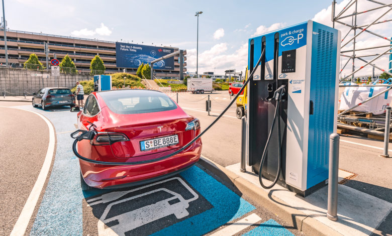 טסלה אדומה חונה בחניה לרכב חשמלי ומחוברת לעמדת טעינה בגרמניה