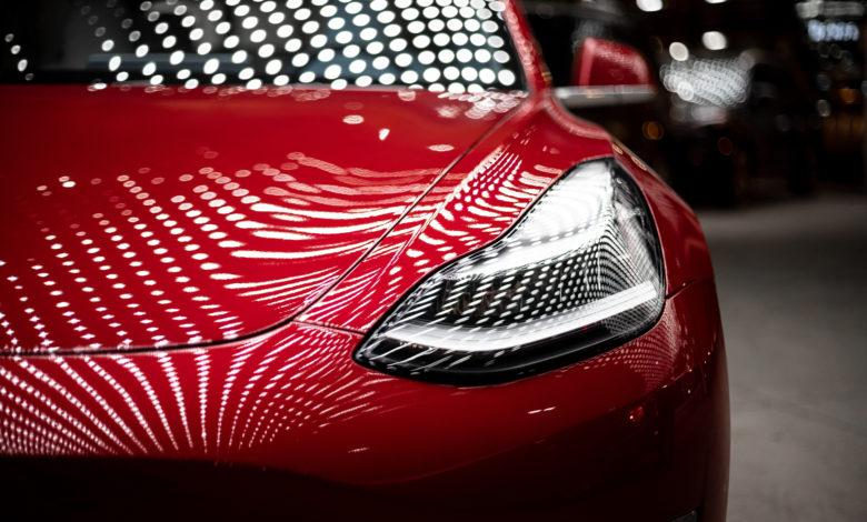 קדמת הרכב של טסלה מודל 3 אדומה, מבט על החלק הקדמי והפנס עם השתקפות החלונות על הרכב