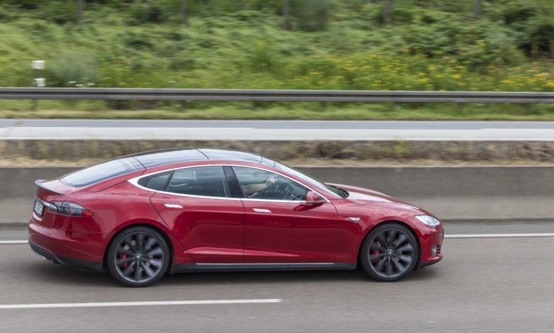 טסלה מודל S בצבע אדום נוסעת בכביש המהיר בגרמניה