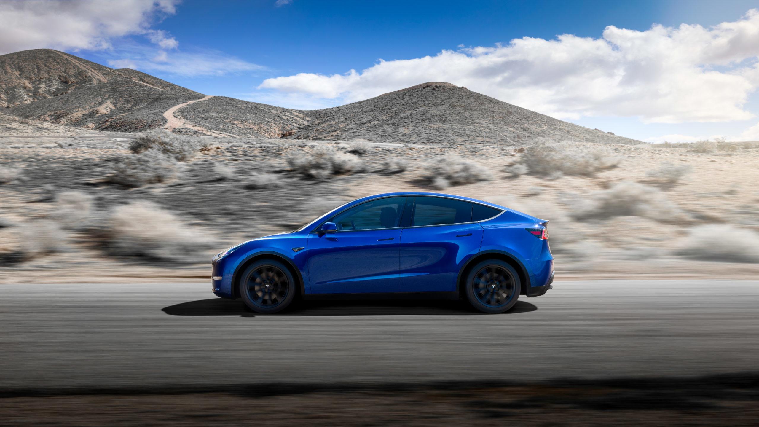 טסלה מודל Y בצבע כחול נוסעת על כביש, מבט מהצד