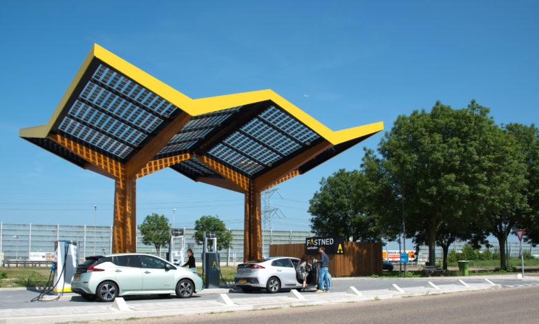 תחנת טעינה עם סככים סולאריים בצבע צהוב עם רכבים חשמליים נטענים