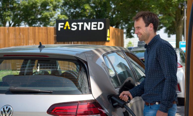 פולקסווגן גולף חשמלית מחוברת לעמדת טעינה של חברת Fastned, עם הלוגו של החברה מאחור