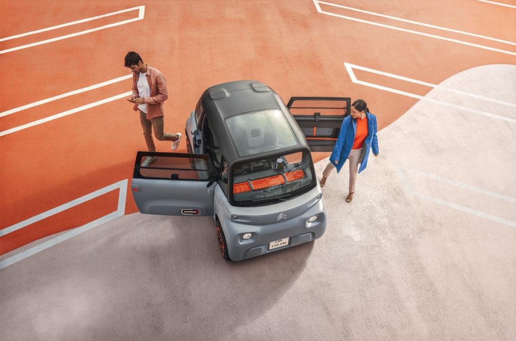 צילום של הרכב החשמלי Ami במבט בלמעלה כשהוא בחניון ושני אנשים עומדים לידו כשדלתותיו פתוחות