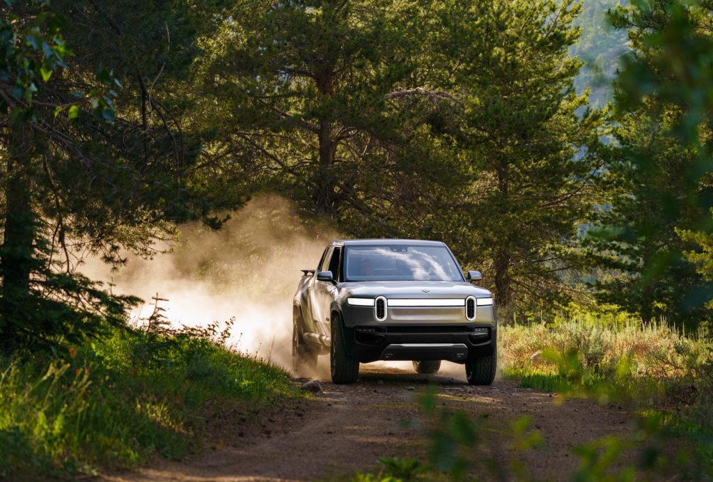 רכב חשמלי של ריביאן, R1t, נוסע בשטח מיוער ומשאיר אבק מאחוריו