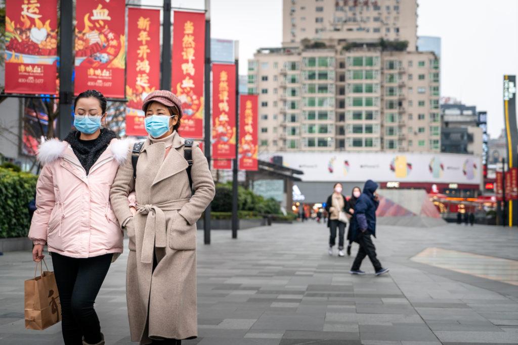 רחוב בסין עם מעט אנשים שיש להם מסכות פנים
