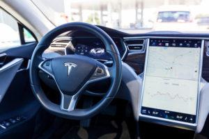 פנים של רכב מסוג טסלה מודל X עם מבט לעבר ההגה ומסך מגע גדול המציג מפה