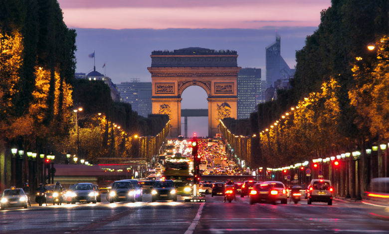 תנועה בשאנז אליזה שפריז בלילה כשברקע שער הניצחון