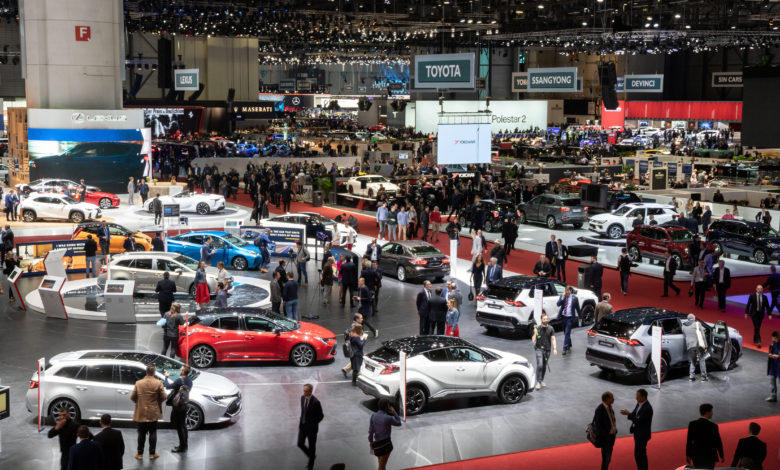 מבט על באולם בתערוכת הרכב בז׳נבה בשנת 2019, עם רכבים במרכז הרחבה ואנשים מסתובבים סביבם