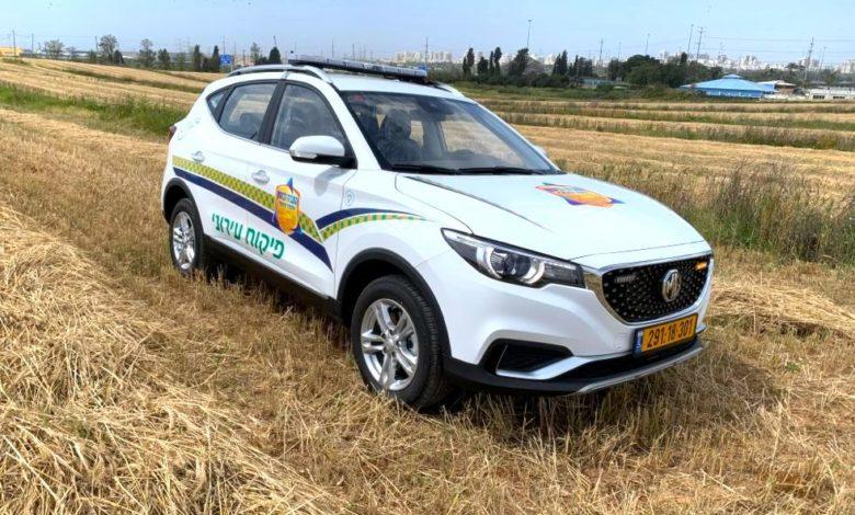ניידת לפיקוח עירוני חשמלית מסוג MG ZS EV בצבע לבן עם כיתוב של עיריית ראשון לציון בשדה