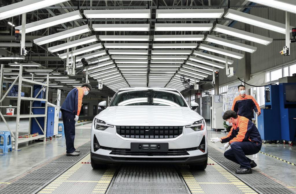פולסטאר 2 בצבע לבן בקו ייצור עם מספר עובדים עומדים ליד הרכב החשמלי
