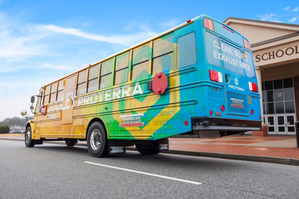 מבט אחורי על אוטובוס חשמלי של חברת Proterra להסעת תלמידים בצבע צהוב מקדים וכחול מאחור