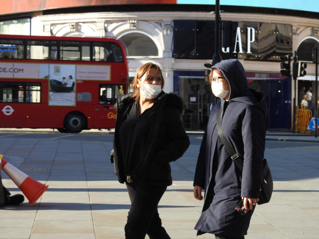 אנשים עם מסכות פנים בשל נגיף הקורונה הולכים ברחובות בלונדון, בריטניה