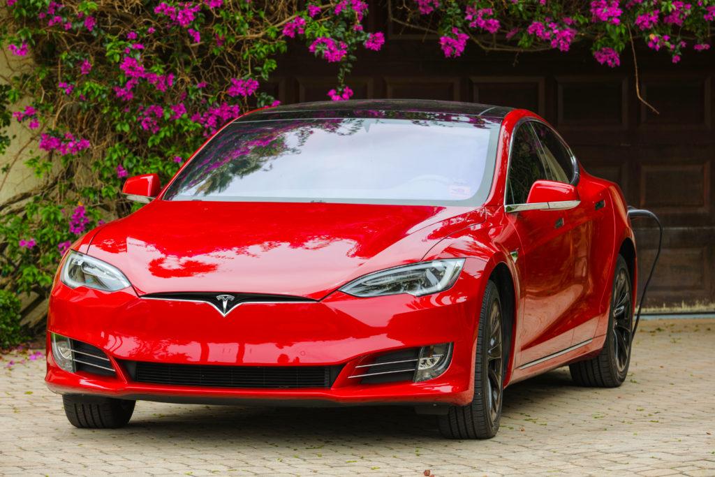 טסלה מודל S בצבע אדום נטענת בחנייה בבית בפלורידה