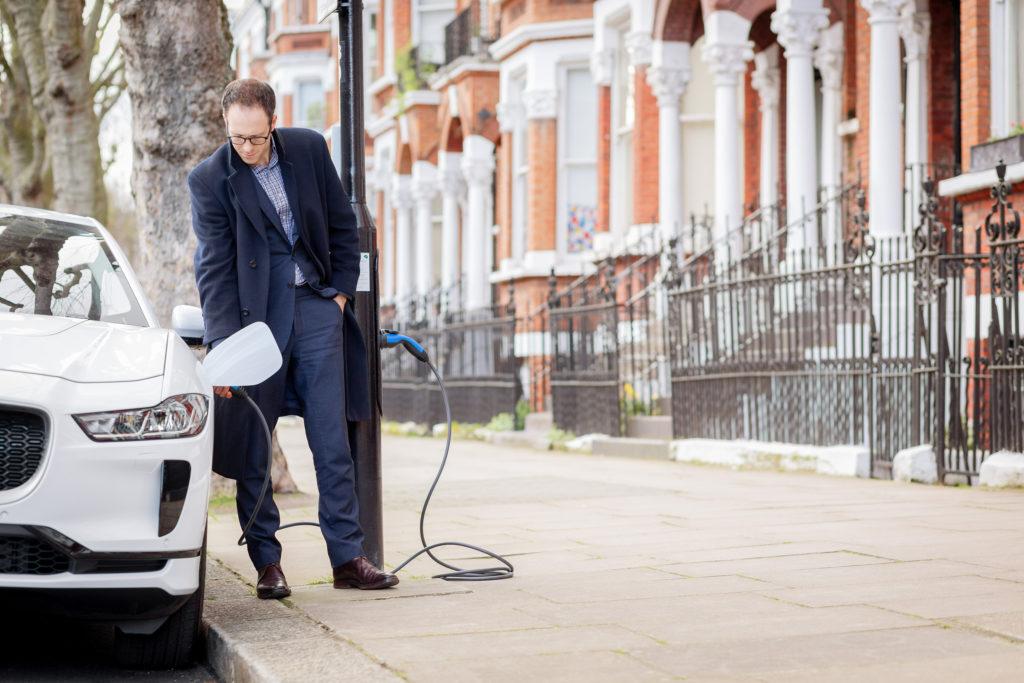 אדם מחבר את רכבו החשמלי לעמוד תאורה שמספק טעינה לרכבים בלונדון בריטניה