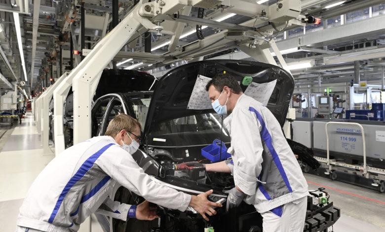 שני עובדים עם מסכות במפעל של פולקסווגן בצוויקאו גרמניה מתקינים פנסים על ה-ID.3