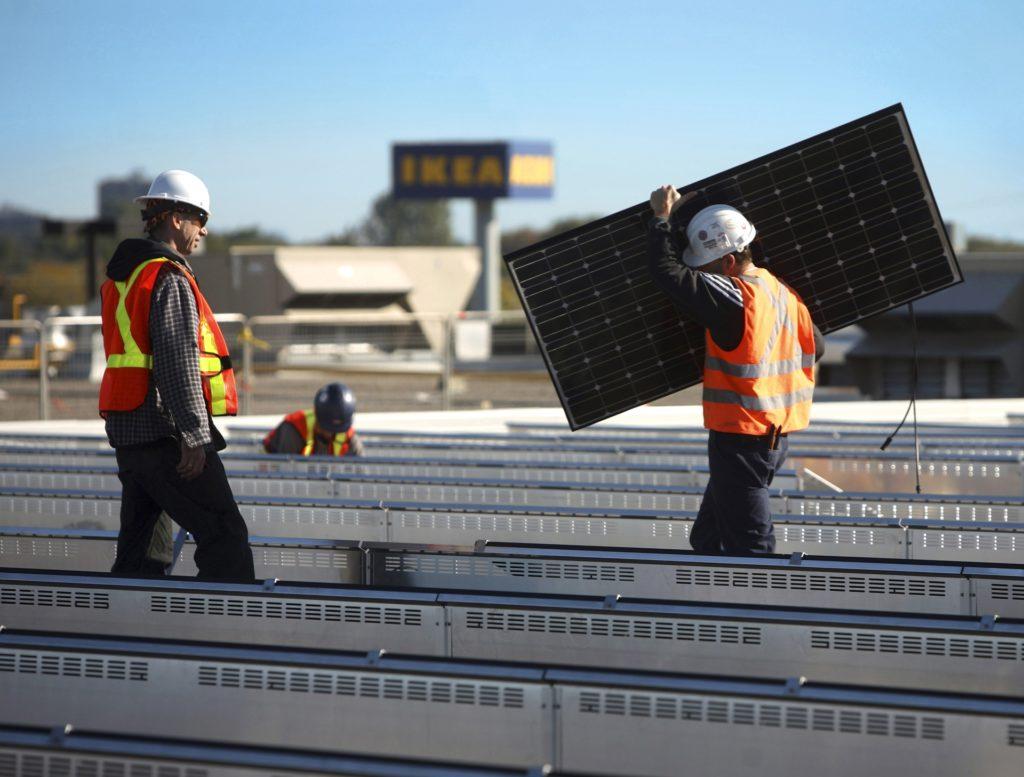 עובדים מתקינים פאנלים סולארים עם הלוגו של איקאה מאחור